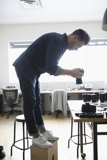 Male photographer standing on box, using digital camera in office - HEROF15552