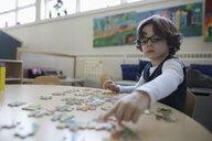 Focused preschool boy assembling jigsaw puzzle in classroom - HEROF15639