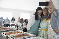 Happy women taking selfie, serving food at soup kitchen community dinner - HEROF15669