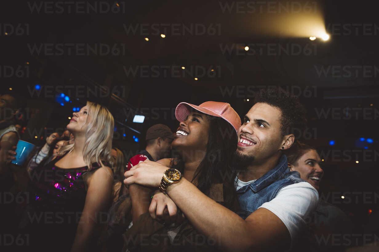 Happy young millennial couple hugging, enjoying music concert at nightclub - HEROF15672 - Hero Images/Westend61