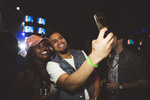 Happy young millennial couple taking selfie with camera phone at nightclub - HEROF15675