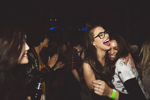 Laughing, happy, carefree young female milennials dancing, partying at nightclub - HEROF15681