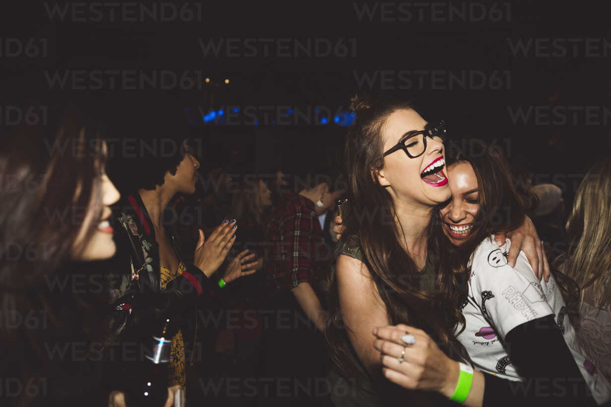Laughing, happy, carefree young female milennials dancing, partying at nightclub - HEROF15681 - Hero Images/Westend61
