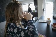 Girl drinking orange juice at dining table - HEROF15702