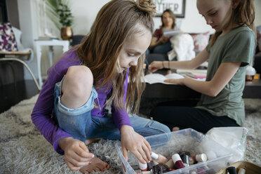 Girl looking, choosing fingernail polish from bin - HEROF15705