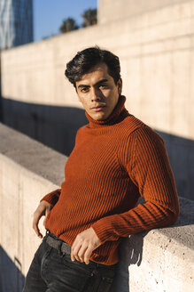 Portrait of fashionable young man wearing turtleneck pullover leaning on a wall at sunlight - AFVF02303