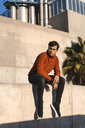 Portrait of fashionable young man wearing turtleneck pullover sitting on a wall at sunlight - AFVF02306