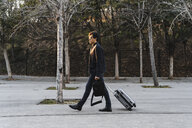 Young businessman with rolling suitcase and backpack - AFVF02330