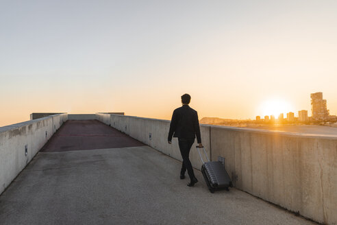 Spain, Barcelona, back view of  young businessman with rolling suitcase at sunset - AFVF02342