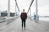 Young man wearing casual clothes standing on a harbor bridge - JRFF02550