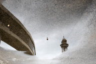 Spain, Barcelona, reflection of a bridge and a cable car in a puddle on the ground - JRFF02574