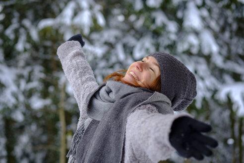 Mädchen mit Mütze und Schal genießt den   Winter im Schnee, Oberbayern, Bayern, Deutschland - LBF02352