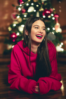 Portrait of laughing teenage girl lying on the floor in front of Christmas tree - ACPF00413