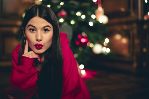 Portrait of teenage girl with Christmas tree in the background pouting mouth - ACPF00416