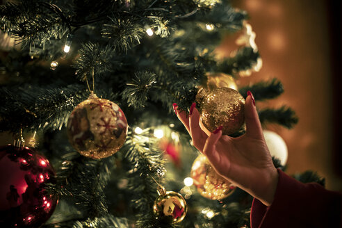 Female hand holding golden Christmas bauble, close-up - ACPF00422