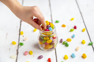 Glass of colourful sweet jellybeans on white wood, hand taking one - SARF04081