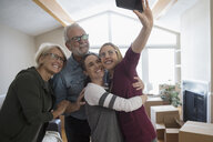 Parents helping affectionate lesbian couple move into new house, taking selfie - HEROF15762