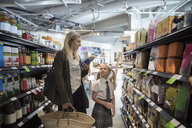 Mother and daughter in school uniform grocery shopping in market aisle - HEROF15807