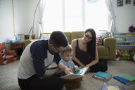Parents reading story book to baby son in living room - HEROF15837