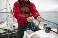 Man adjusting rigging rope on sailboat - HEROF15879
