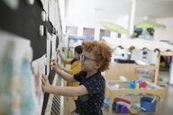 Preschool boy hanging painting on wall - HEROF15963