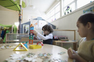 Preschool boy playing with building blocks in classroom - HEROF15969