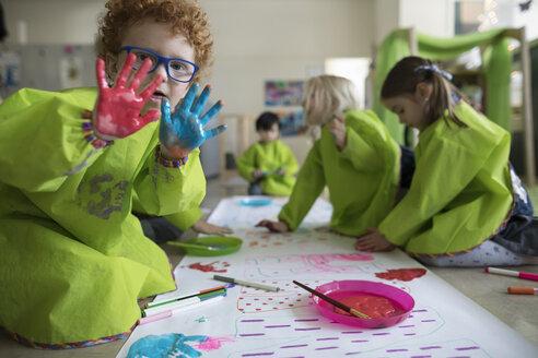 Portrait preschool boy in smock showing finger paint on hands at poster in classroom - HEROF16017