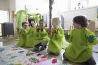 Playful preschool students in smocks showing finger paint on hands at poster in classroom - HEROF16020