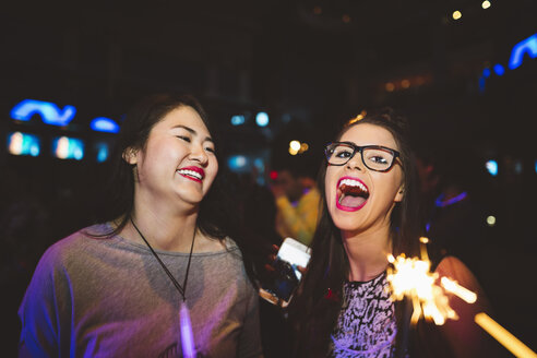Portrait enthusiastic, laughing young female milennials partying in nightclub - HEROF16044
