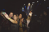Playful, happy female millennial friends taking selfie with camera phone at music concert in nightclub - HEROF16056