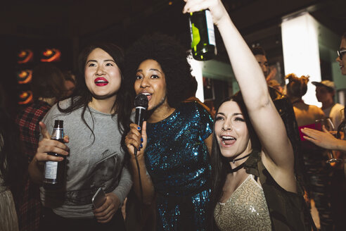 Playful young female millennial friends drinking beer and singing karaoke at nightclub - HEROF16062