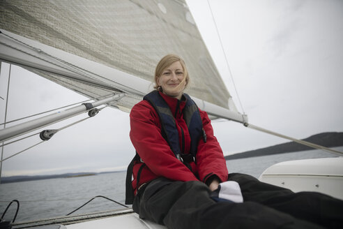 Portrait smiling, confident woman sitting on sailboat - HEROF16092