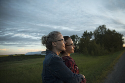 Affectionate mother and daughter farmers looking away on farm at sunset - HEROF16107