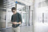 Brunette businessman using digital tablet in office lobby - HEROF16122