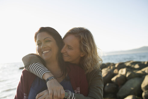 Affectionate lesbian couple smiling and hugging on sunny ocean beach - HEROF16170