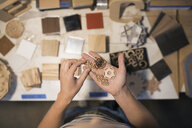 View from above female craftswoman examining laser cut wood pieces - HEROF16221