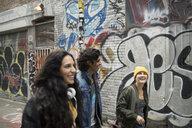 Young friends walking in urban alley along graffiti buildings - HEROF16239