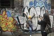 Young woman with camera phone photographing friend along graffiti wall - HEROF16242