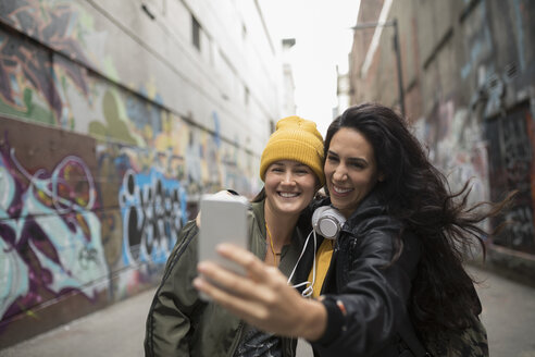 Young women friends with camera phone taking selfie in urban graffiti alley - HEROF16248