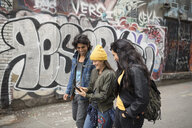 Young friends texting with smart phone in urban graffiti alley - HEROF16251