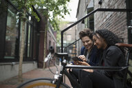Young couple texting with smart phone on urban stoop - HEROF16254