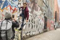 Young woman with camera phone photographing man climbing post along urban graffiti wall - HEROF16278