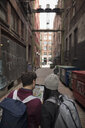 Young couple with backpacks looking at digital map on digital tablet in urban alley - HEROF16281