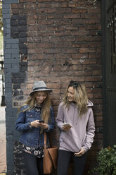 Young women friends texting with smart phones along brick wall - HEROF16287