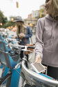 Young woman with smart phone using bicycle sharing system on urban street - HEROF16293