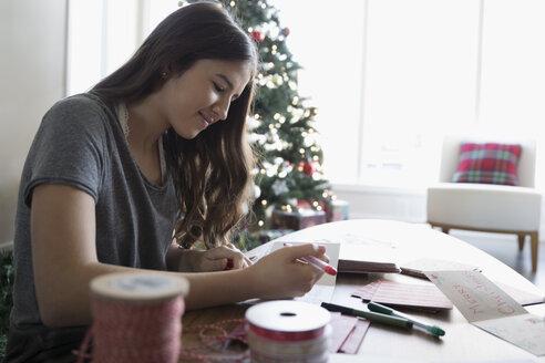 Teenage girl making Christmas cards in living room - HEROF16332