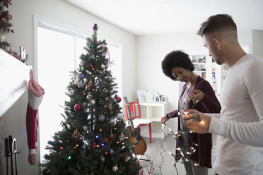 Young couple decorating, hanging Christmas lights on tree in living room - HEROF16338
