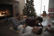 Young couple in pajamas laying, relaxing by fire near Christmas tree in living room - HEROF16344