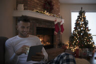 Young man in pajamas relaxing, using digital tablet near fire and Christmas tree in living room - HEROF16347