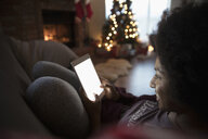 Young woman relaxing, using digital tablet near fire and Christmas tree in living room - HEROF16350